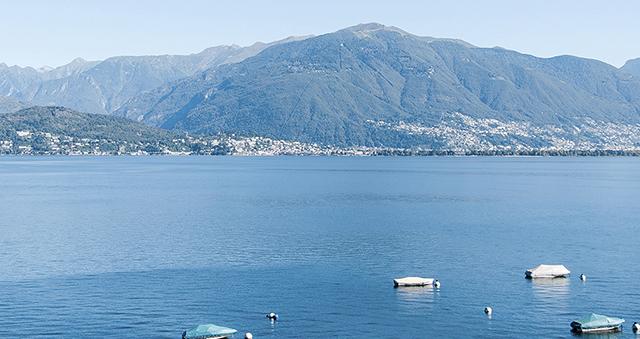 Veduta di lago con barche e montagne sullo sfondo
