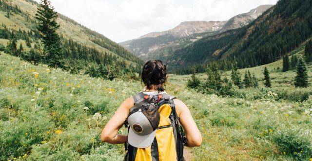 Persona con zaino in spalle ripresa di schiena in mezzo alla natura