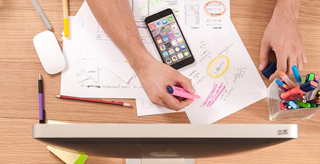 Dall'alto, due braccia su un tavolo con cellulare, fogli e schermo pc