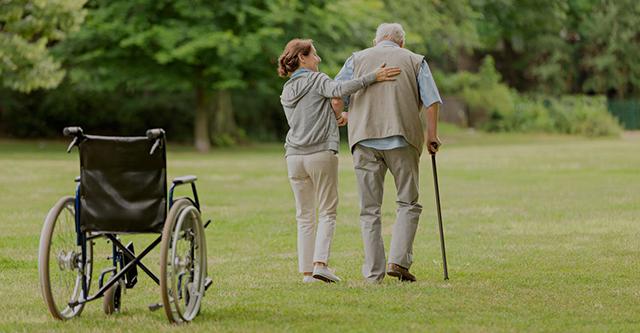 Donna accompagna uomo anziano al parco, carrozzina sulla sinistra