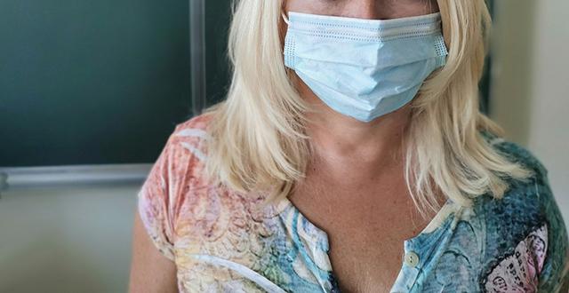 Docente in aula con mascherina ritratta dal naso in giù