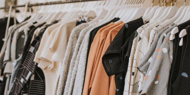 Fila di vestiti e maglie appesi su espositore - Fashion Revolution