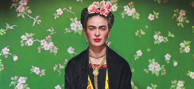 Ritratto fotografico di Frida Kahlo, golf nero, collane e fiori rosa in testa, sfondo verde con fiori