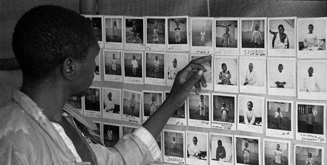 Foto i bianco e nero con uomo di colore che guarda fotografie appese al muro - genocidio Ruanda