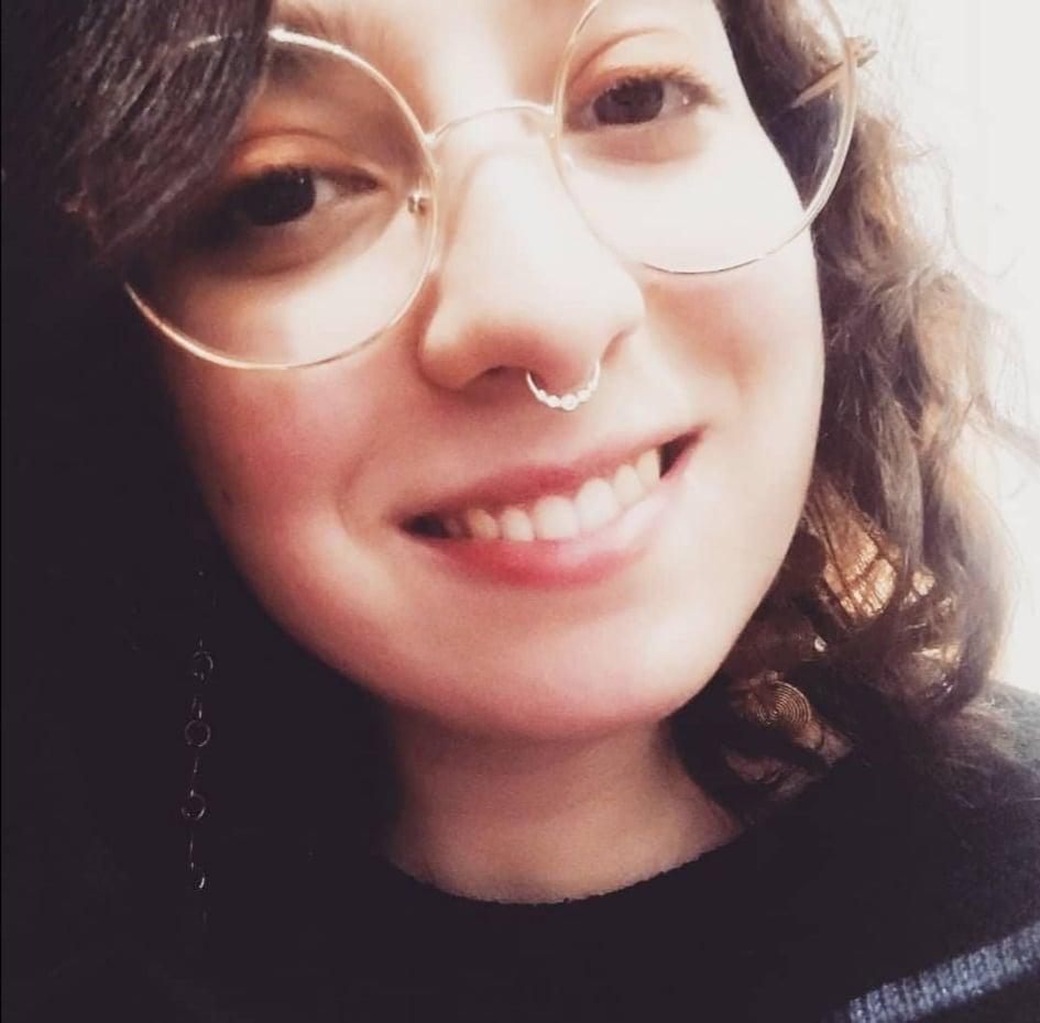 Ragazza sorridente con occhiali tondi e piercing al naso