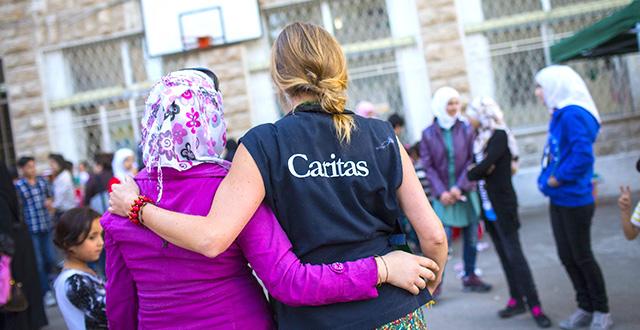 Operatrice Caritas con migrante, di schiena