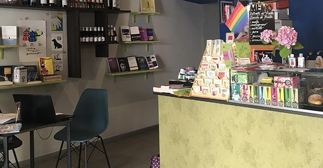 Bancone caffetteria con bandiera arcobaleno, tavolino con sedie e scaffale con libri - libreria Nora Book & Coffee