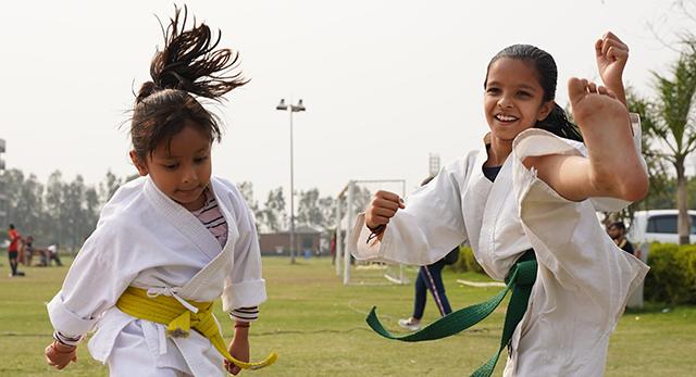 Due bambine che praticano arti marziali all'aperto