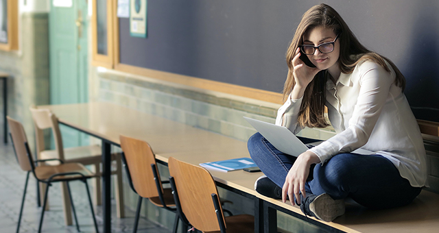 Ragazza con portatile seduta su un banco davanti a una lavagna