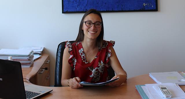 Ragazza con capelli lunghi, occhiali e vestito rosso seduta a scrivania - musicoterapeuta Giulia Merli