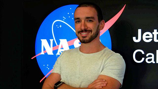 Ragazzo sorridente in maglietta bianca e braccia conserte davanti a logo Nasa - Stefano Cappucci