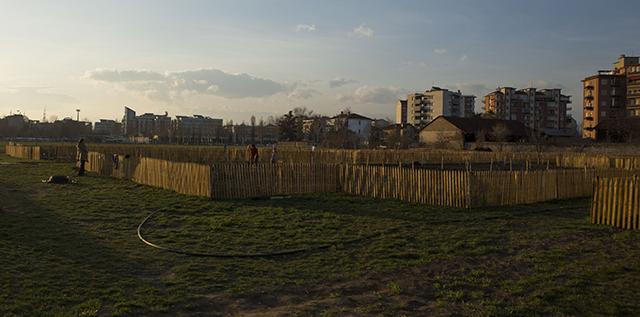 Terreni agricoli recintati con sfondo di città - Orti Generali