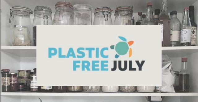 Cartello Plastic Free July davanti a barattoli di vetro