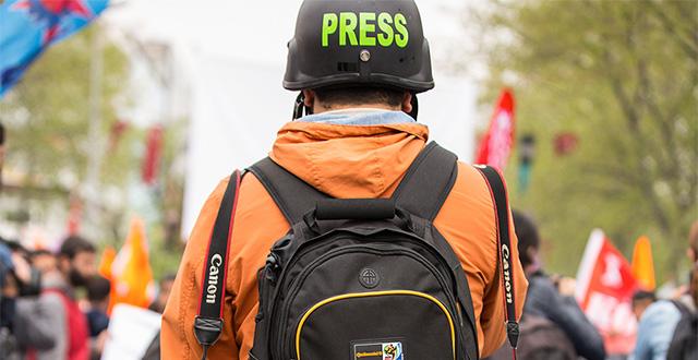 Giornalista di schiena con caschetto e scritta Press