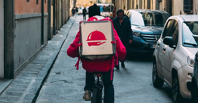 Rider in bici visto di schiena con scatola cubica sulle spalle