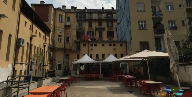 Cortile fra palazzi con gazebi, tavoli e sedie - Casa del Quartiere San Salvario