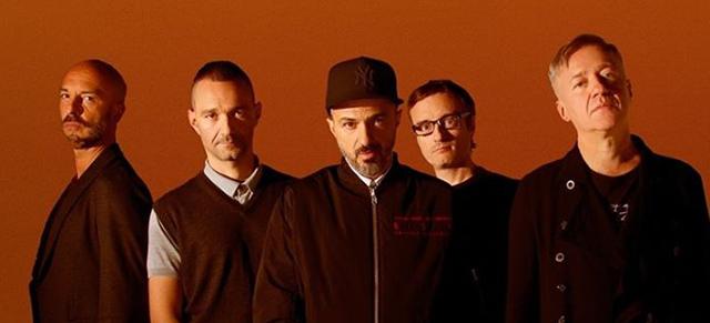Cinque uomini in piedi su fondo arancione - Subsonica