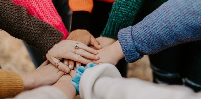 Mani che si uniscono una sull'altra in segno di solidarietà