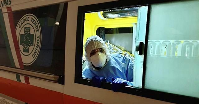 Persona con tuta protettiva, mascherina e guanti affacciata a finestrino ambulanza Croce Verde Torino