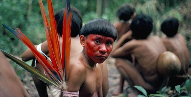 Indigeno a petto nudo con volto dipinto di rosso e piume colorate