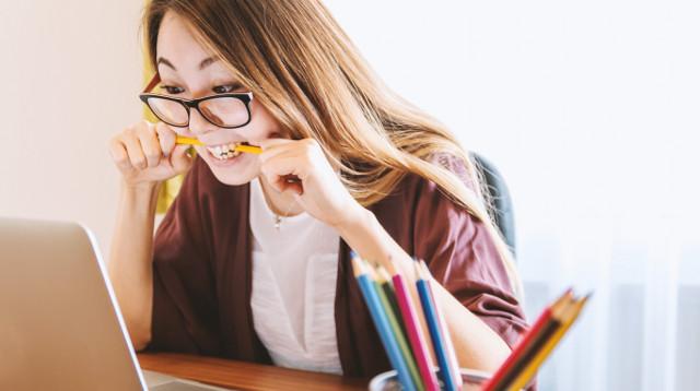 Ragazza al computer con matita in bocca e aria preoccupata