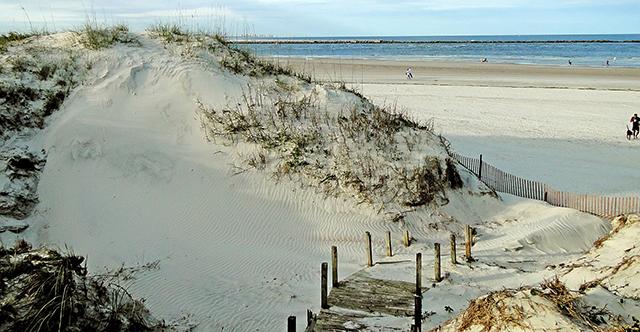 Duna di sabbia e passerella di legno vicino a spiaggia