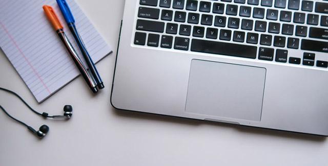 Penne, cuffiette e portatile si tavolo bianco