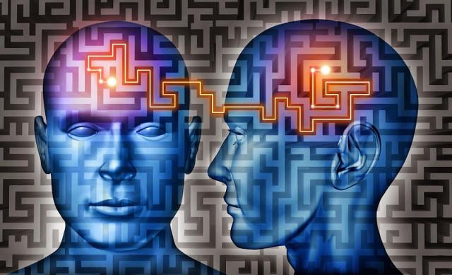 Volto umano disegnato in blu da davanti e di profilo con linea arancione che collega i cervelli - mentalismo